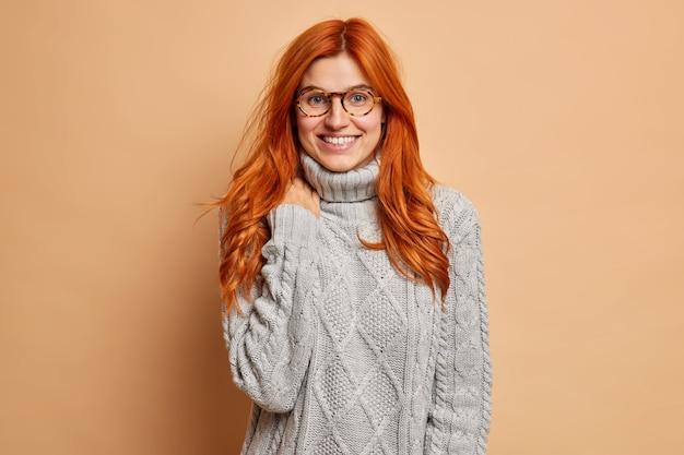 Angenehm aussehende rothaarige junge frau lächelt breit hört etwas sehr angenehmes hat freundliches gespräch mit bester freundin trägt warmen winterpullover.