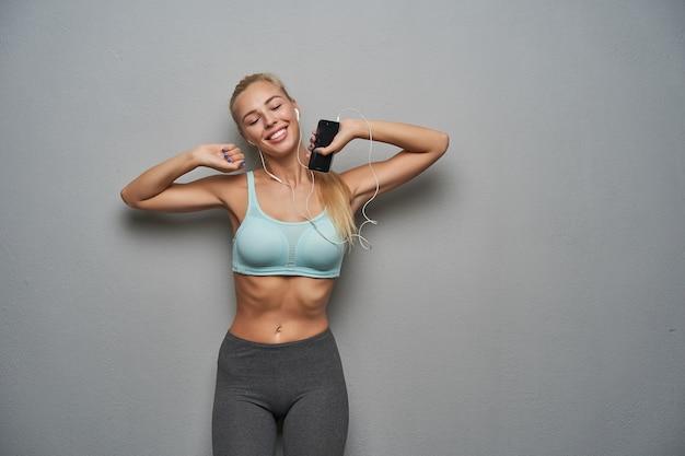 Angenehm aussehende schläfrige junge schlanke blonde dame mit lässiger frisur, die sich vor dem morgendlichen training streckt, die augen geschlossen hält und positiv lächelt, während sie über grauem hintergrund posiert