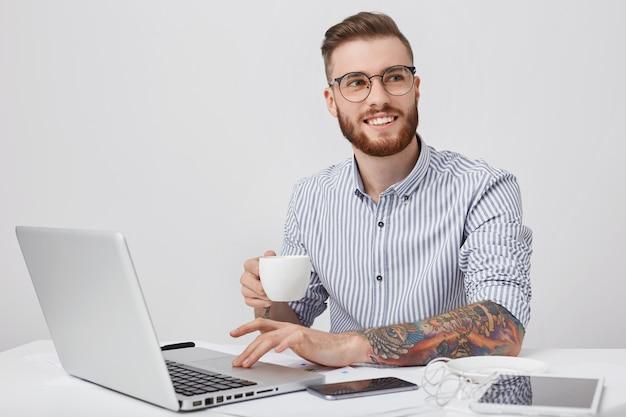Angenehm aussehende stilvolle tätowierte männliche unternehmer oder büroangestellte