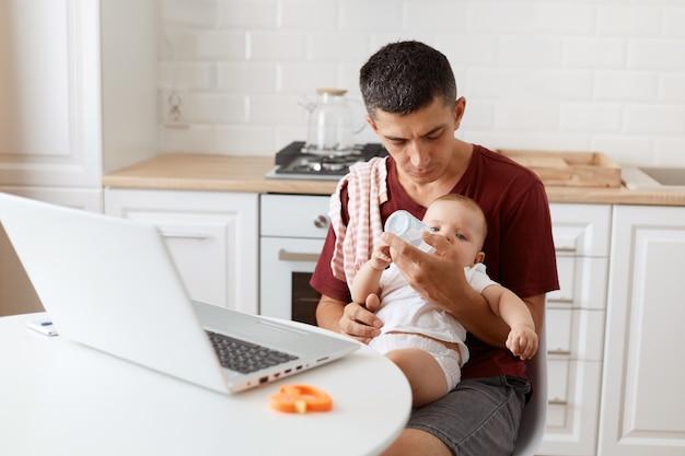 Angenehm aussehender dunkelhaariger, gutaussehender mann, der ein lässiges t-shirt mit einem handtuch auf der schulter trägt, mit laptop am tisch sitzt, ein baby in den händen hält und babywasser zum trinken gibt.