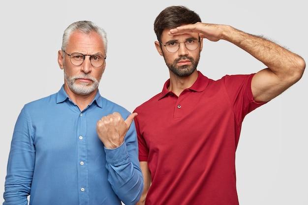 Angenehm aussehender erfolgreicher bärtiger alter geschäftsmann im eleganten hemd zeigt mit dem daumen auf seinen sohn, der die hand in der nähe der stirn hält und aufmerksam in die ferne schaut, erklärt über familienunternehmen