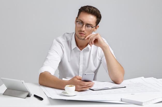 Angenehm aussehender männlicher architekt schaut ernsthaft in tablet-computer, arbeitet mit notizen und skizzen, trinkt kaffee, ist sehr beschäftigt. talentierter junger männlicher ingenieur arbeitet am bauprojekt