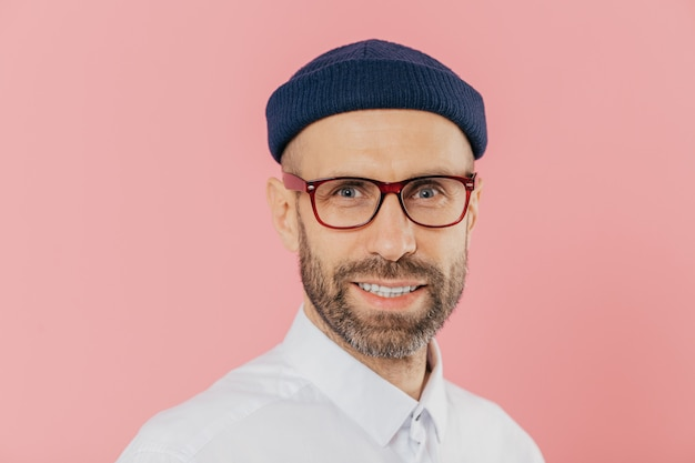 Angenehm aussehender unrasierter mann trägt eine brille, lächelt sanft, schaut mit zufriedenem gesichtsausdruck in die kamera
