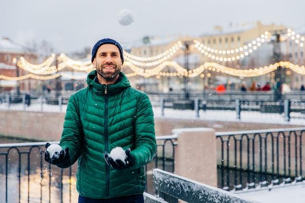 Angenehm aussehendes männliches modell hält schneebälle in den händen, um kampf zu haben