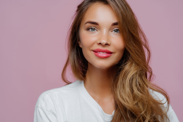 Angenehm aussehendes weibliches model hat ein zartes lächeln, trägt minimales make-up, hat langes gewelltes haar und schaut in die kamera
