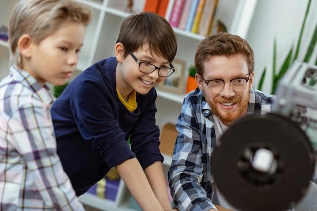 Angenehm inspirierter lehrer, der seinen schülern während eines interessanten ingenieurkurses den mechanismus des 3d-druckers vorstellt