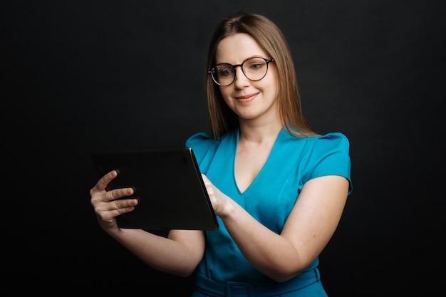 Angenehme attraktive involvierte frau, die lächelt und gadget benutzt, während sie im internet surft und gegen schwarze wand steht