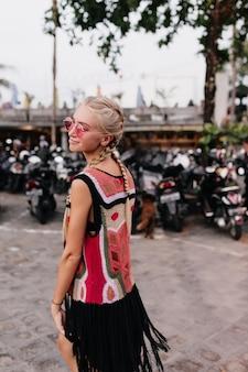 Angenehme blonde frau in stilvoller strickkleidung. niedliches blondes weibliches modell mit zöpfen, die auf unscharfem hintergrund mit sanftem lächeln aufwerfen.