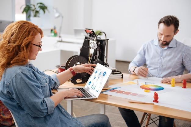 Angenehme entzückte attraktive frau, die auf den laptopbildschirm schaut und die statistiken studiert, während sie im büro arbeitet