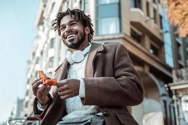 Angenehme gefühle. erfreulicher internationaler mann, der ein lächeln auf seinem gesicht hält, während er kuchen isst