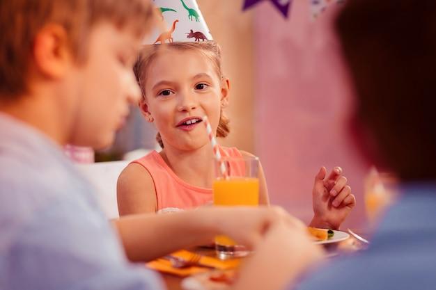 Angenehme gefühle. erstaunliches kind, das lächeln auf ihrem gesicht hält, während es mit freunden kommuniziert