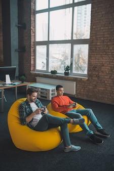 Angenehme glückliche männer, die videospiele zusammen spielen, während sie zu hause entspannen