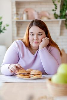 Angenehme, gut aussehende frau, die in der küche sitzt, während sie einen burger nimmt?