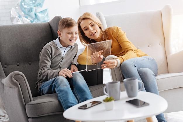 Angenehme interaktion. erfreute nette positive frau, die auf dem sofa sitzt und mit ihrem sohn spricht, während sie ihm etwas interessantes auf dem tablet zeigt