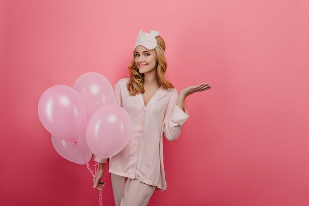 Angenehme junge frau im seidennachtanzug, die auf party in ihrem geburtstag wartet. anmutiges mädchen mit blondem gewelltem haar, das mit lächeln auf heller wand aufwirft.