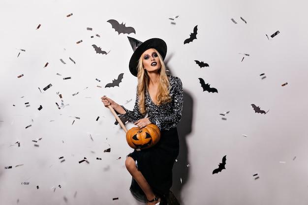 Angenehme junge hexe, die mit fledermäusen an der wand aufwirft. hübsches blondes vampirmädchen, das halloween-kürbis hält.