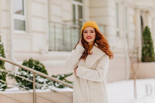 Angenehme kaukasische frau im weißen kittel, der wochenendspaziergang genießt. außenporträt des stilvollen ingwermädchens im winteroutfit.