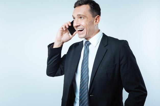 Angenehme kommunikation. erfreut netter männlicher unternehmer, der ein telefon hält und ein gespräch führt, während er über die arbeit spricht