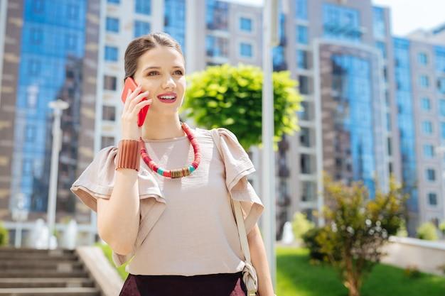 Angenehme kommunikation. freudige angenehme frau, die lächelt, während sie mit ihrem freund am telefon spricht
