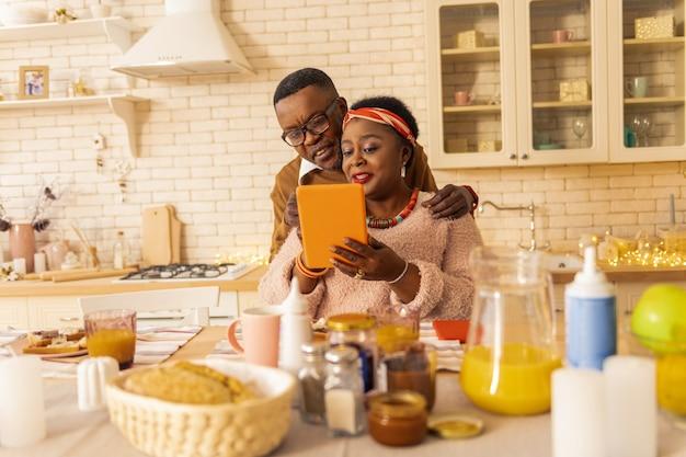 Angenehme kommunikation. nette afroamerikanische frau, die mit ihrem ehemann spricht, während sie ihm den tablettbildschirm zeigt