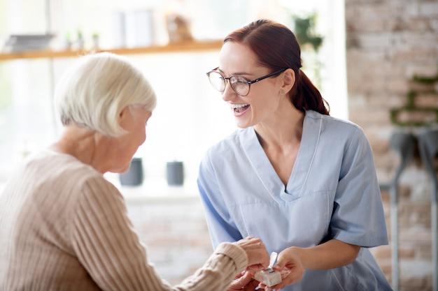 Angenehme krankenschwester lacht, während sie mit der pensionierten dame spricht