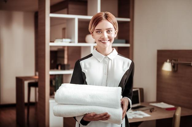 Angenehme magd. junges angenehmes blondes hotelmädchen, das weiße handtücher während der arbeit hält