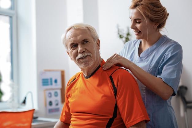 Angenehme massage. fröhlicher alter mann, der sich sehr wohl fühlt, während er seine massage genießt