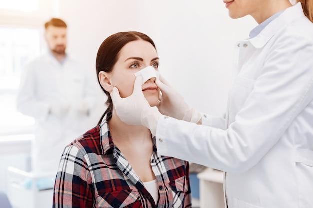 Angenehme nette junge frau, die einen medizinischen verband auf ihrer nase hat und den kosmetischen chirurgen ansieht, während er nach einer rhinoplastischen operation ist