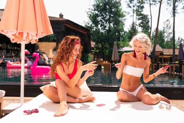 Angenehme unterhaltung. erfreute freudige frauen, die auf dem strandbett sitzen, während sie karten zusammen spielen