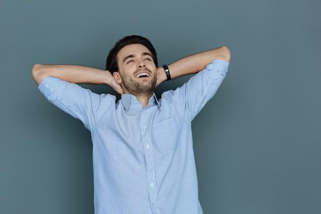 Angenehme zeit. glücklicher freudiger positiver mann, der hände unter den kopf legt und lächelt, während er seine ruhe genießt Premium Fotos
