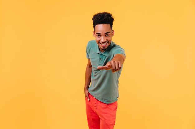 Angenehmer afrikanischer mann, der finger zeigt. innenaufnahme des interessierten schwarzen jungen, der aufwirft.