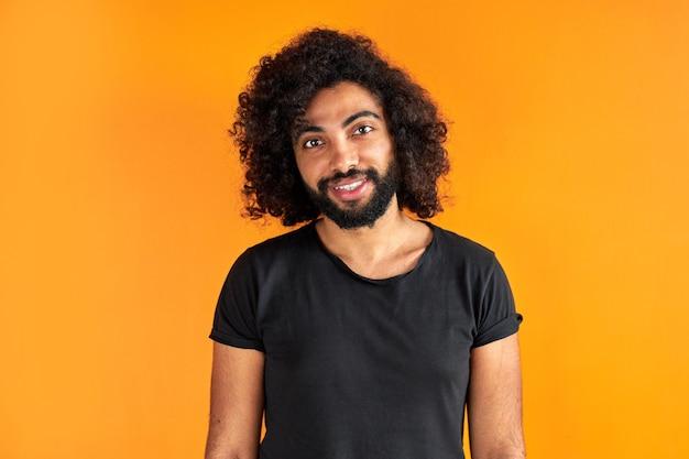 Angenehmer indischer arabischer mann im hemd, das kamera betrachtet, hat freundlichen blick, aufgeschlossenen kerl lokalisiert auf orange hintergrund