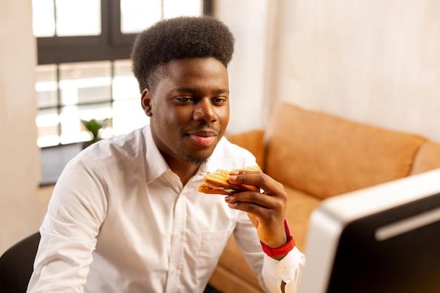 Angenehmer junger mann, der ein leckeres sandwich hält, während er an seinem arbeitsplatz zu mittag isst