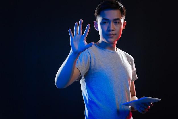 Angenehmer junger mann, der eine tafel hält, während er seine hand auf den virtuellen bildschirm drückt