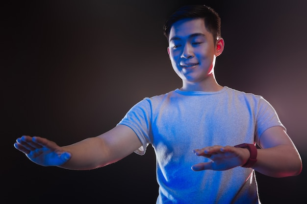 Angenehmer junger mann, der seine hände betrachtet, während er eine virtuelle tafel benutzt