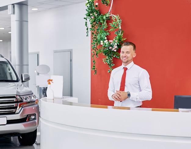 Angenehmer kaukasischer verkäufer begrüßt kunden im autohaus