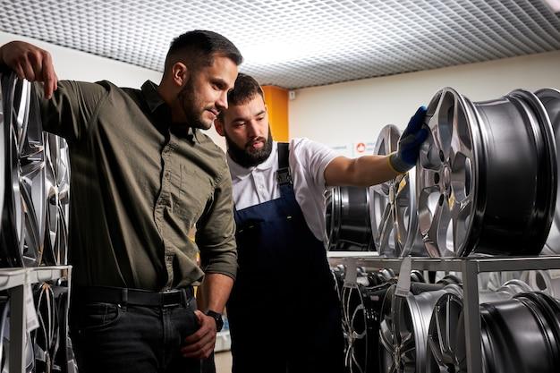 Angenehmer kunde und selbstbewusster automechaniker, der im laden über autoräder spricht und zwischen felgenständern steht