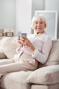 Angenehmer morgen. angenehme ältere frau, die auf der couch sitzt und beim halten einer tasse tee aufwirft