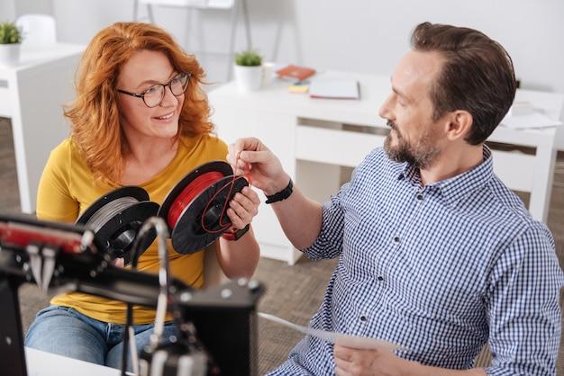 Angenehmer netter positiver mann, der filament hält und seine qualität überprüft, während er mit 3d-technologie arbeitet