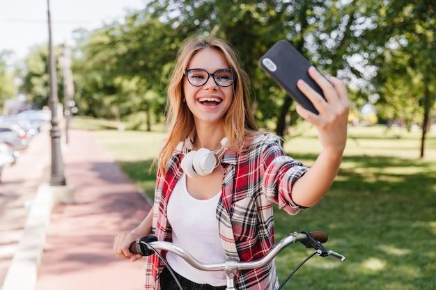 Angenehmes blondes mädchen, das smartphone für selfie im park verwendet. charmante lächelnde dame in gläsern, die auf fahrrad fahren.