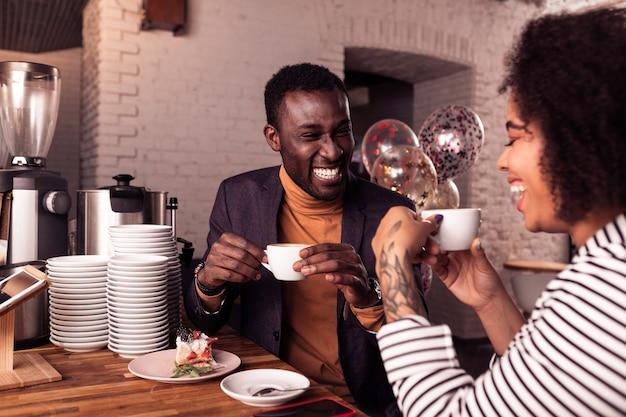 Angenehmes date. glückliches positives paar, das zusammen kaffee trinkt, während auf dem datum ist