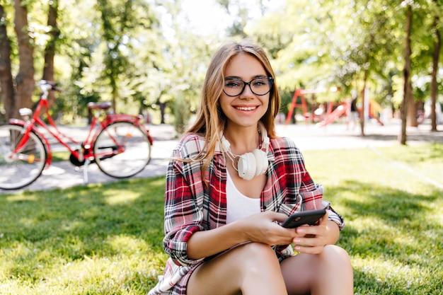 Angenehmes europäisches weibliches modell, das telefon beim sitzen auf rasen verwendet. kaukasisches gutaussehendes mädchen, das mit smartphone im park aufwirft.