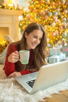 Angenehmes gespräch. hübsche junge frau, die ein online-date hat und sich zufrieden fühlt