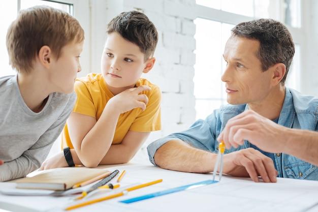 Angenehmes gespräch. schöne jugendliche jungen, die im büro ihres vaters am tisch sitzen und mit ihm sprechen, während er an einer blaupause arbeitet und einen kompass benutzt