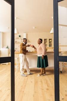 Angenehmes getränk. erfreutes afroamerikanisches paar, das miteinander spricht, während es seinen tee genießt