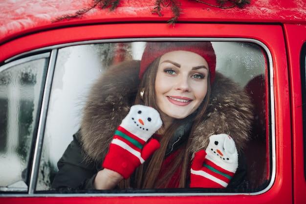 Angenehmes modisches wintermädchen lächelnd, das an rotem weinleseauto, das von schneeflocken mittlerer schuss umgeben ist, posiert. schöne junge frau, die dezember-weihnachtsferien genießt, die positive emotionen haben