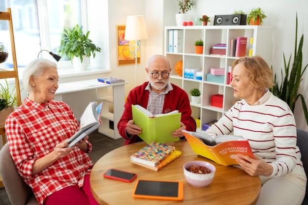 Angenehmes treffen. nette alte leute, die um den tisch sitzen und gemeinsam bücher lesen?