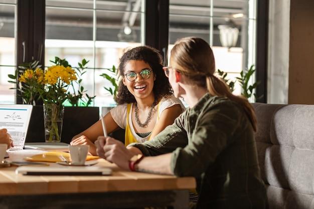 Angenehmes zusammenspiel. fröhliche junge frau, die lächelt, während sie mit ihrer freundin im café spricht