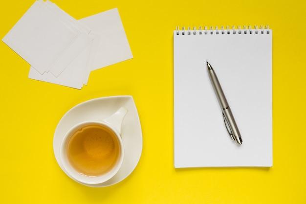 Angeredete gelbe schreibtischtabelle der fotografie mit leerem notizbuch, computer, versorgungen und t-stück schale.
