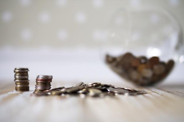 Angesammelte münzen, die in haufen auf dem holzboden gestapelt sind